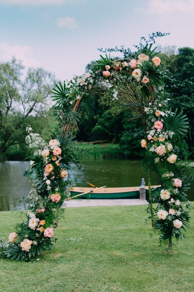 A tropical wedding with ceremony arch by Jo Flowers.