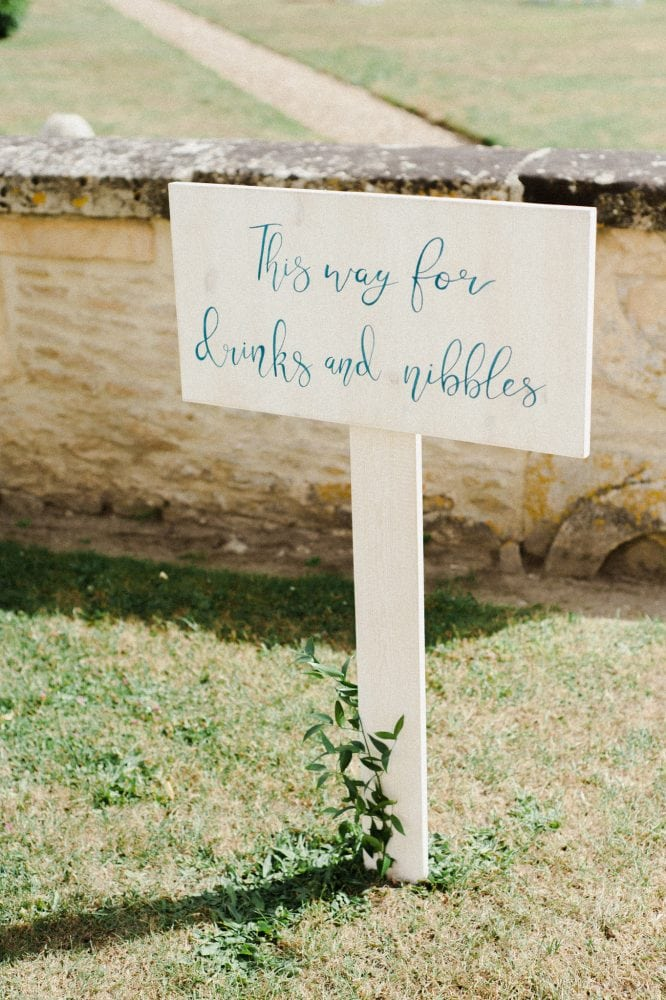 White wooden staked wedding signage with blue writing at a wedding in Normandy France by Knot & Pop