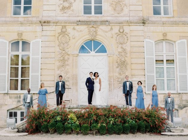 Bride, groom, ushers and maids on the steps of a chateau in Normandy France